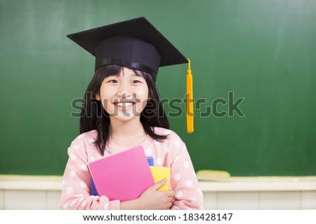 smiling girl wear a graduation hat and holding books - stock photo
