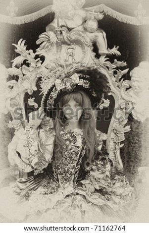 Smiling girl wearing an antique princess dress and hat (sitting on a princess throne), vintage style - stock photo