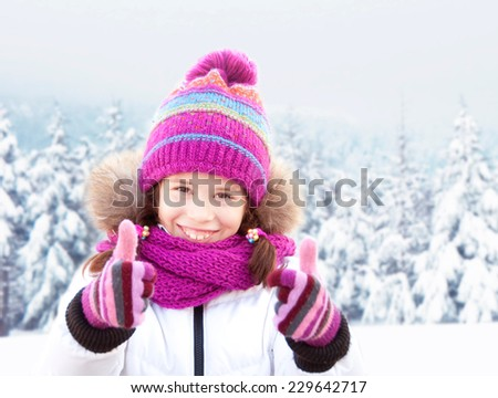 Smiling girl wearing hat, scarf and gloves with her thumbs up - stock photo