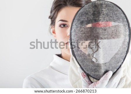 Smiling girl wearing white fencing costume holding the fencing mask - stock photo