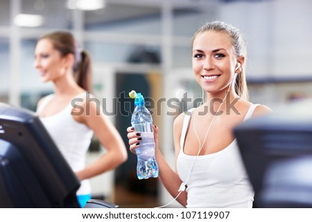 Smiling girl with a bottle of water - stock photo