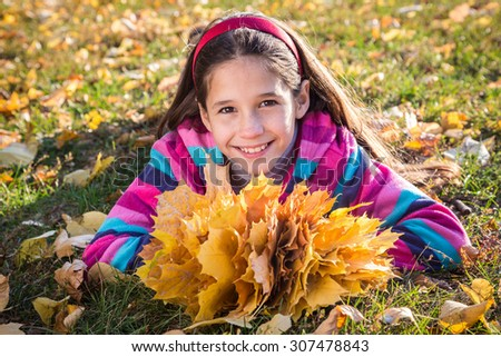 Smiling girl with autumn leaves in sunny park - stock photo