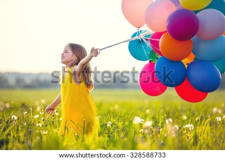 Smiling girl with balloons in the field - stock photo