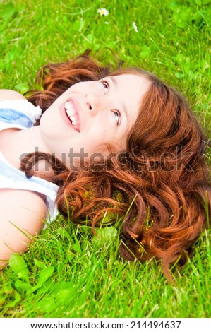 Smiling girl with beautiful red hair lying on grass - stock photo