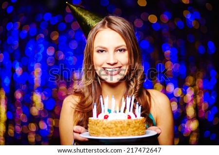Smiling girl with birthday cake looking at camera on sparkling background - stock photo