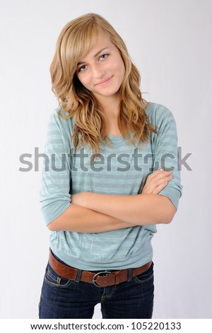 Smiling Girl with Crossed Arms. Thirteen year old girl standing with her arms crossed. Looking at the viewer while smiling. Note: Not Isolated. - stock photo
