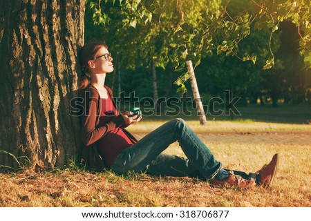 Smiling girl with cup of tea or coffee enjoying near park tree in morning sunlight - stock photo