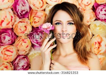 Smiling Girl with Flower on Blossom Background. Woman Fashion Model with Coloring Hairstyle, Manicure and Makeup - stock photo