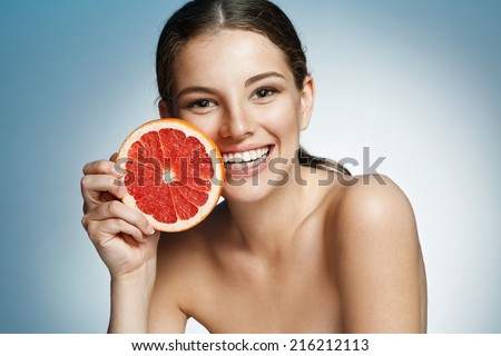 Smiling girl with grapefruit cut in half fruit in hand, with pomelo slice, natural organic raw fresh food concept  - stock photo