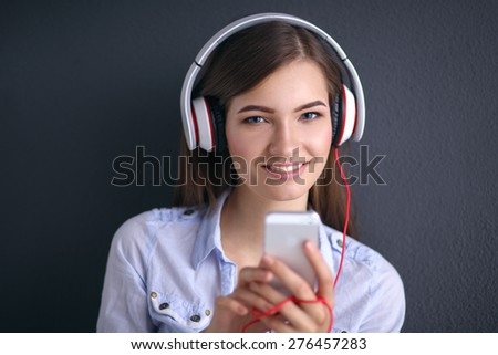 Smiling girl with headphones sitting on the floor near wall - stock photo