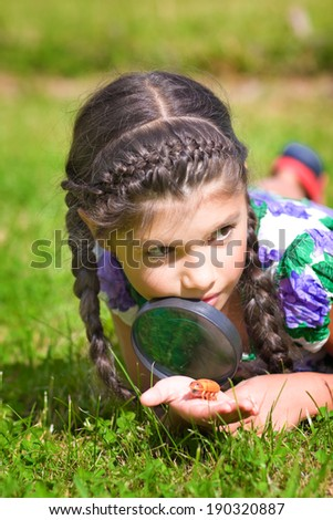 Smiling girl with magnifying glass and beetle - stock photo