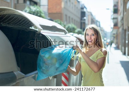 Smiling girl with rubbish near refuse collection container - stock photo