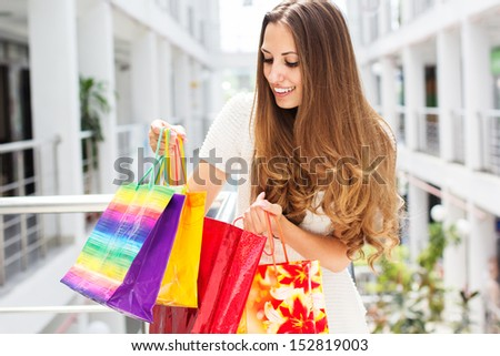 Smiling girl with shopping bags in mall - stock photo