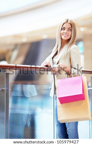 Smiling girl with shopping bags in store - stock photo