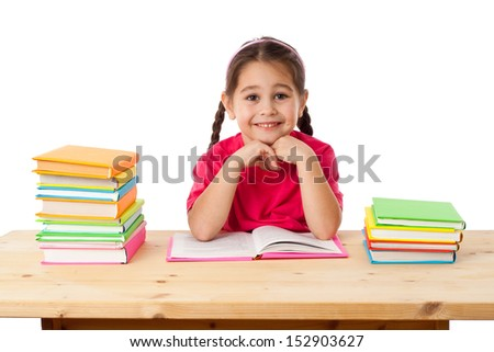 Smiling girl with stack of books on the desk, isolated on white - stock photo