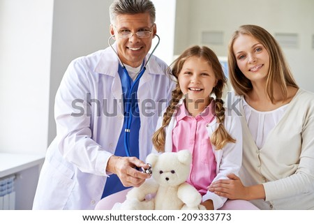Smiling girl with teddy bear, her mother and doctor looking at camera in clinics - stock photo
