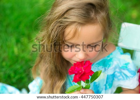 smiling girl with the bouquet of roses sits on a bench - stock photo
