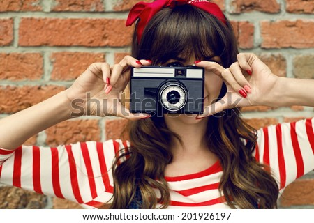 smiling girl with vintage camera taking photo on brick wall background  - stock photo
