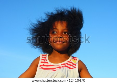 Smiling  girl with wind blowing through her hair - stock photo