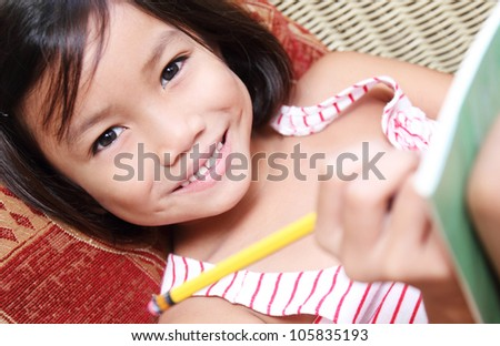 Smiling girl writing with pencil - stock photo