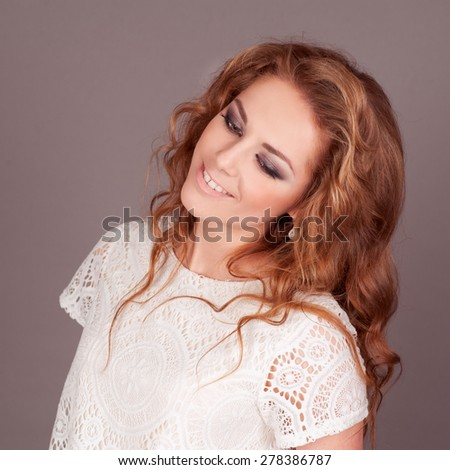 Smiling girl 20-22 year old in room over grey. Wearing casual white shirt. Long curly hair. Young adults.  - stock photo