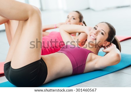 Smiling girls at the gym doing abs workout exercises on a mat and looking at camera, fitness and training concept - stock photo