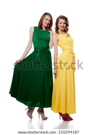 Smiling girls posing in stylish colorful dresses - stock photo