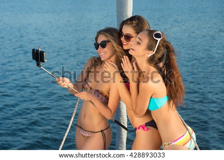 Smiling girls take a selfie. Ladies taking selfies on yacht. We're having so much fun. Vacation time spent at sea. - stock photo
