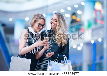 Smiling girls with mobile in a store - stock photo