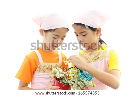 Smiling girls with plant - stock photo