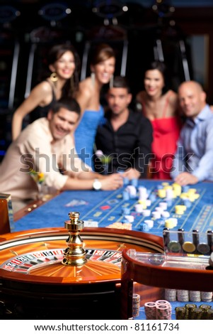 smiling glamourous friends watching the spinning roulette - stock photo