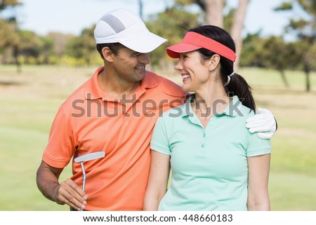 Smiling golfer couple with arm around while standing on field - stock photo