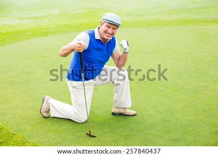 Smiling golfer kneeling on the putting green on a sunny day at the golf course - stock photo