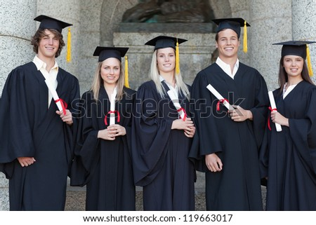 Smiling graduates posing in front of the university - stock photo