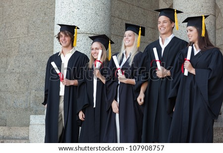 Smiling graduates posing while holding their diploma in front of the university - stock photo