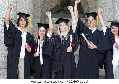 Smiling graduates posing while raising arms in front of the university - stock photo