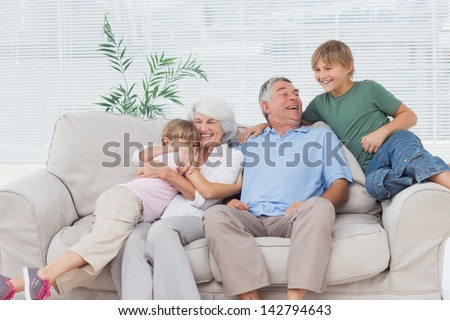 Smiling grandchildren embracing their grandparents on couch - stock photo