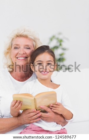 Smiling granddaughter and grandmother reading a novel together on the sofa - stock photo