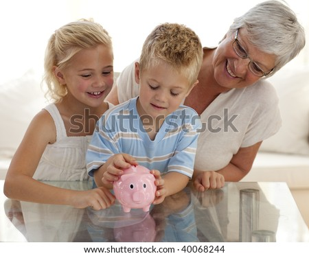 Smiling grandmother and children saving money in a piggybank - stock photo