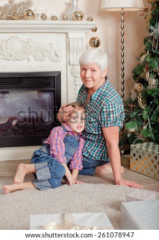 Smiling grandmother and granddaughter sitting on the floor at home during the Christmas holidays - stock photo