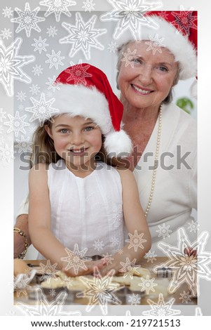 Smiling grandmother and little girl baking Christmas cakes against snowflakes on silver - stock photo