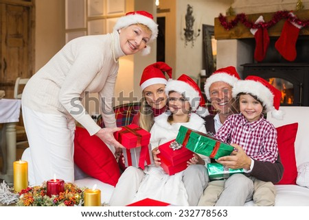 Smiling grandmother giving gift to her family at home in the living room - stock photo