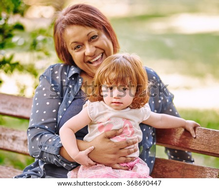 Smiling grandmother holding her granddaughter on her lap while sitting on a park bench outdoors - stock photo