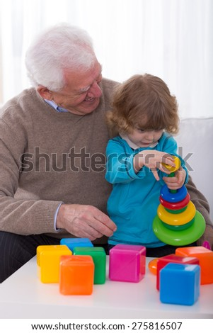 Smiling grandpa and grandchild building color tower - stock photo