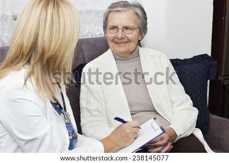 Smiling gray haired  grandmother with crossed fingers sitting on the sofa and talking with her mature female doctor at home. - stock photo