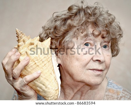 Smiling great grandmother listening to a seashell - stock photo