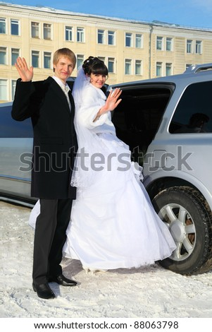 smiling groom and bride stand near wedding limousine, waving their arms and sit down in car at winter outdoors - stock photo