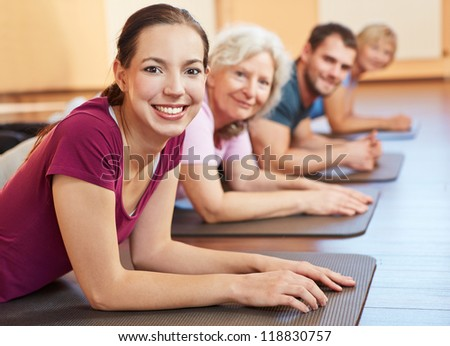 Smiling group exercising together in a fitness center - stock photo