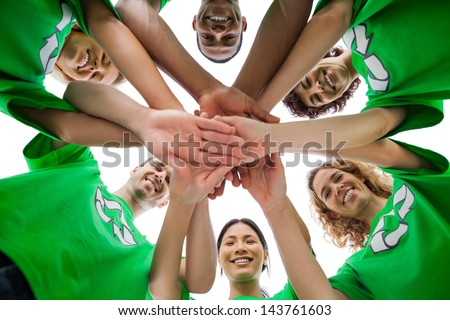 Smiling group of activists piling up their hands on white background - stock photo
