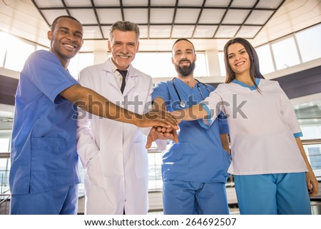Smiling group of doctors. Teamwork.  In hospital. Looking at camera. - stock photo